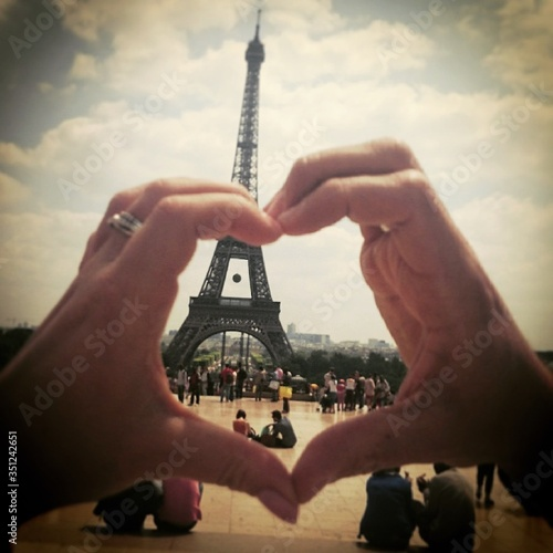 Fototapeta Cropped Hand Making Heart Shape Against Eiffel Tower And Cloudy Sky On Sunny Day obraz