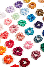 Cropped Detailed Shot Of A Set Of Colorful Scrunchies Made Of Velvet Fabric. The Bright Hair Holders Are Located Diagonally On The White Background.