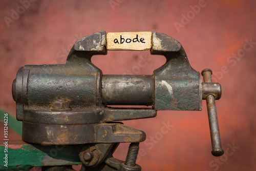 Vice grip tool squeezing a plank with the word abode Canvas Print