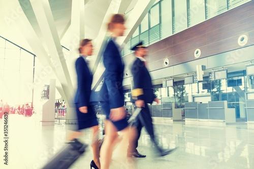 Mature pilot with young beautiful flight attendants walking in airport Billede på lærred