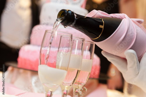 Photo filling champagne glasses served by hand with white gloves to toast