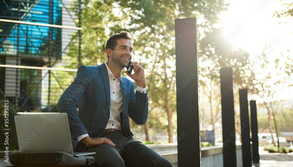 Fototapeta Smiling businessman talking on a cellphone outside his office building