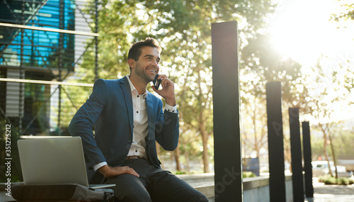 Fototapeta Smiling businessman talking on a cellphone outside his office building obraz