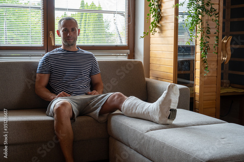Foto Man with broken leg recovering at home