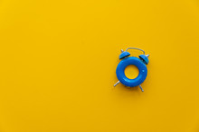 Vacation Time. Blue Alarm Clock As Swimming Ring Form On Yellow Background. Top View. Copy Space