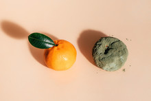 Fresh And Rotten Mandarins. Spoiled Tangerines With Green Mold And Fungus And A Ripe Fresh One With A Leaf On Coral Background.