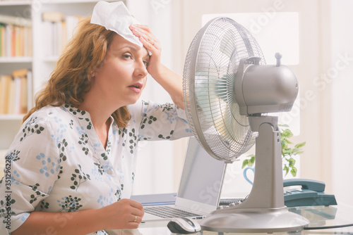 Fotografering Woman suffers from heat in the office or at home