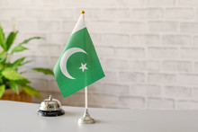 Silver Vintage Bell With National Flag Of Pakistan On Reception Desk With Copy Space. Hotel Service. Travel, Tourism. Selective Focus. Asia, Concept.