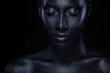 Woman with black body paint. Cheerful young african girl with bodypaint. An amazing model with art makeup. Closeup face.