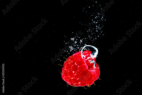 Fototapeta Close-up Of Raspberry Splashing In Water Against Black Background obraz na płótnie