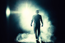 Full Length Of Silhouette Man Walking Against Bright Light At Night