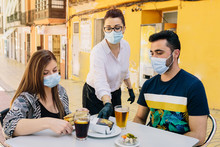 Clients With Masks On The Terrace Of A Bar In Spain Attended By A Waiter With Gloves And Masks. Social Distancing During Phase One Of De-escalation. Coronavirus