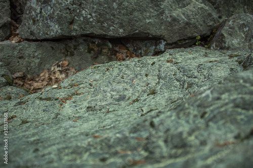 Obraz Zbliżenie na skałę z granitu, porośniętą mchem ze śladami brudu i korozji - fototapety do salonu