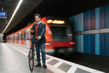 Businessman With Bicycle Text Messaging On Smart Phone While Standing On Platform Against Subway Train