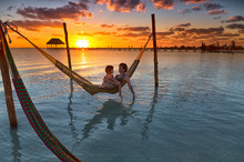 Mother And Daughter Relaxing On Hammock At Beach During Sunset In Holbox Island, Cancun, Mexico