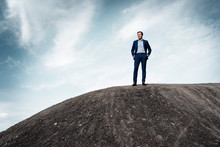 Mature Businessman Standing On Top Of A Disused Mine Tip