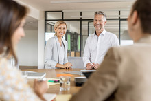 Smiling Businesswoman And Businessman Leading A Meeting In Office