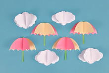 Rainy Weather Concept With Paper Craft Clouds And Pink And Yellow Umbrellas On Blue Background