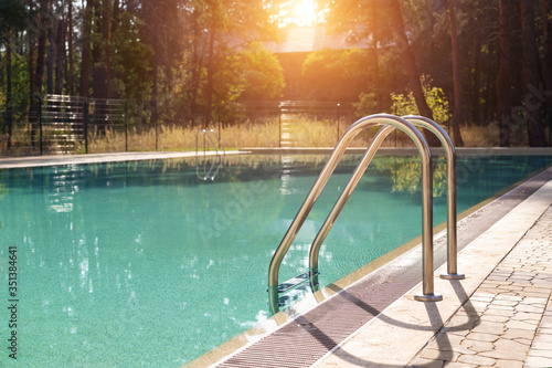 Fototapeta Big luxury empty rectangular swimming pool with clean blue water and ladder at tropical forest beach resort at sunrise morning light and nobody outdoors. Healthy leisure lifestyle travel and exercise obraz