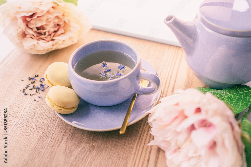Fototapeta Tea cup home serving for one english black tea black tea with teapot and macarons cookies with lovely pink peonies flowers decoration.