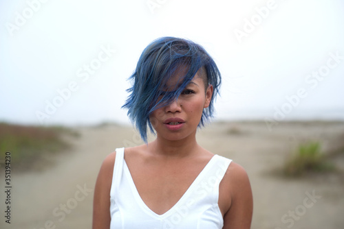 Portrait of funky attractive young woman in white dress and cool blue hair looki Canvas Print