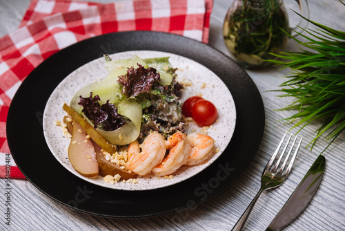 Fotografija Salad with flambe shrimps, slices of fresh cucumber and a drunken pear, with cherry tomatoes