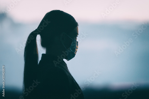 Obraz Coronavirus COVID-19 anxiety mental health problem sad woman wearing protective medical face mask silhouette alone thinking of the depressive future of society. - fototapety do salonu