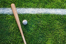 High Angle View Of Baseball Bat With Ball On Grassy Field