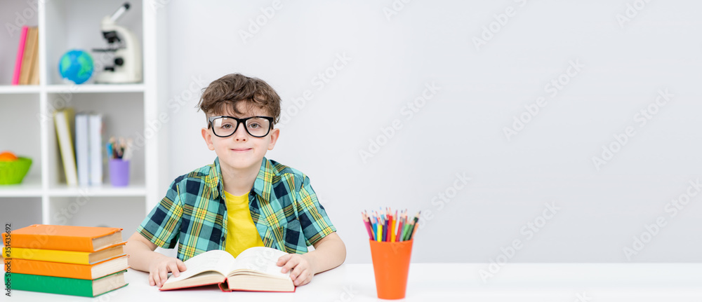 Fototapeta Smiling clever boy wearing eyeglasses sits with open book at home. Empty space for text