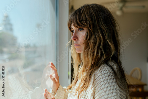 Tableau sur Toile Sad woman staring out the window during a lockdown