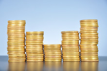 Stacks Of Gold Coins On Table Against White Background