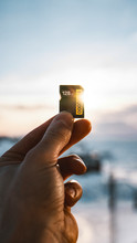 Hand Holding A Memory Card Against The Sunlight