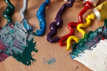 Close-up Of Colorful Paints Spilled From Tubes On Wooden Table