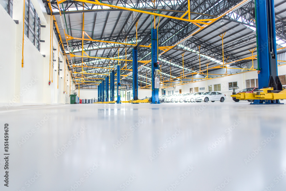 Fototapeta The interior decoration is an epoxy floor of an industrial building or a large automobile repair center with a steel roof structure that is built in an industrial factory.