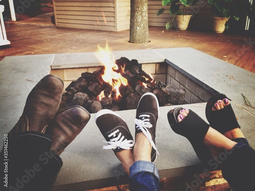 Fototapeta Low Section Of Family Relaxing By Fire Pit obraz