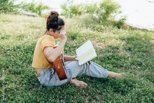 songwriter create and writing notes,lyrics in the book on grass at parks beside the sea and building city background Canvas Print