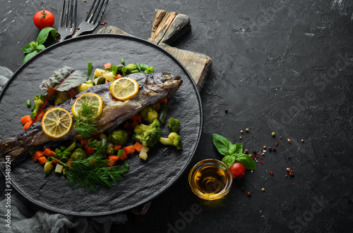 Fototapeta Baked trout fish with vegetables and lemon on a black plate. Top view. Free copy space. obraz