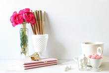 Office Supplies With Candies And Flower Vase On Desk Against White Wall