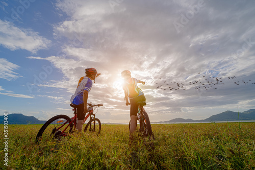 Fototapeta family couple lover enjoy the life of biking on the fresh field meadow grass, cheerfully life together outdoors obraz
