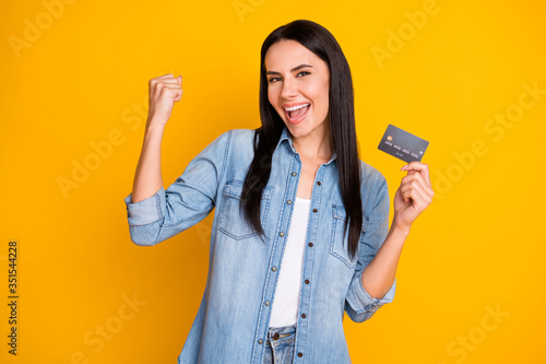 Obraz Close-up portrait of nice attractive lovely pretty cute cheerful cheery girl holding in hand cell plastic card new solution novelty advert isolated bright vivid shine vibrant yellow color background - fototapety do salonu