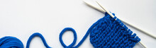 Top View Of Blue Wool Yarn And Knitting Needles On White Background, Panoramic Orientation