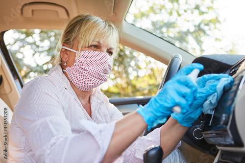 Obraz Cleaner cleans dashboard in rental car because of corona virus - fototapety do salonu