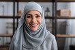 Leinwanddruck Bild - smiling muslim woman in hijab looking at camera in living room, domestic violence concept