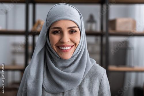 smiling muslim woman in hijab looking at camera in living room, domestic violenc Fotobehang