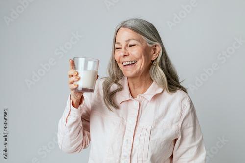 Cheerful senior woman drinking a glass of milk