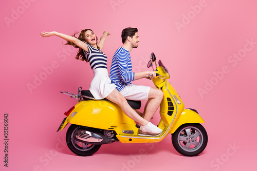 Obraz Profile side view portrait of his he her she nice attractive carefree cheerful cheery couple riding moped spending weekend vacation journey having fun isolated on pink pastel color background - fototapety do salonu