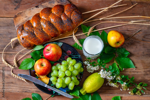Fototapeta Wicker bun, lemon, apples, green grapes, wheat and a glass with milk on a wooden table. Jewish holiday Shavuot. obraz