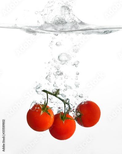 Billede på lærred Cherry Tomatoes Splashing In Water