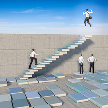 Businesspeople, Some Of Them Have Created A Ladder With Books On The Ground To Overcome The Wall