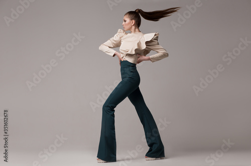 Fashionable look, a woman in long green flared trousers, a silk beige blouse with wide magnificent sleeves. A model poses in a studio on a light background, her hair is flying. Fashion clothes.